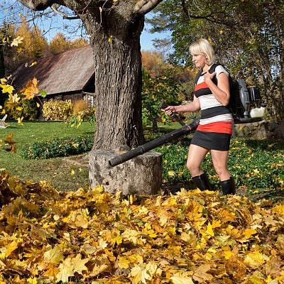Mujer usando un soplador de hojas a gasolina con mochila