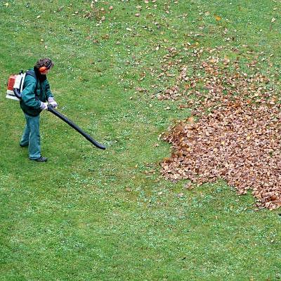 Persona soplando hojas con un soplador, aspirador y triturador